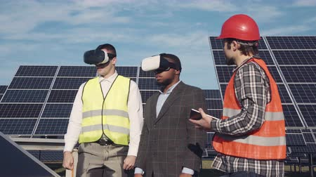 devise : Three men standing in solar power station and using virtual reality glasses. Copyspace.