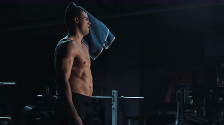 черные волосы : Strong toned young athlete towelling off in a gym wiping away sweat after doing a strenuous workout showing off his muscular physique, with copy space