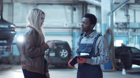 mechanika : Female blond client giving keys from her car to mechanic in uniform and signing on digital tablet Dostupné videozáznamy