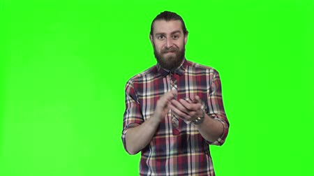 choise : Bearded man giving a thumbs up gesture of approval or success with a smile, upper body in a plaid shirt on a colorful green background with copy space