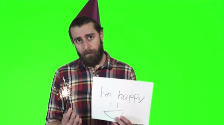 preguiça : Bearded man in a plaid shirt with sparkle in his hand and holds up a i am happy sign at the camera over a green background with copy space.