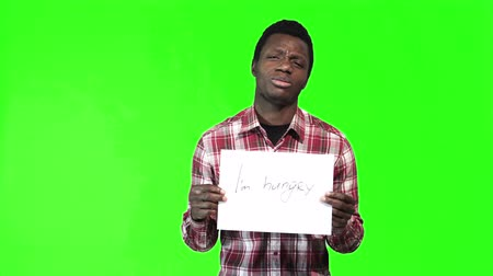 preguiça : African man in a plaid shirt holds up a i am hungry sign at the camera over a green background with copy space.