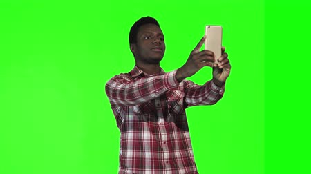tuşları : African young man make selfie using smartphone on green screen