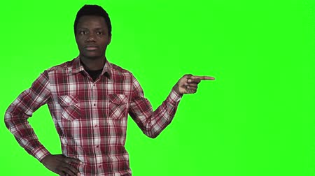 точка зрения : Modern african man pointing with both hands towards blank copy space on a bright green background, upper body side view