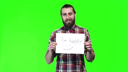 preguiça : Bearded in a plaid shirt holds up a i am happy sign at the camera over a green background with copy space.