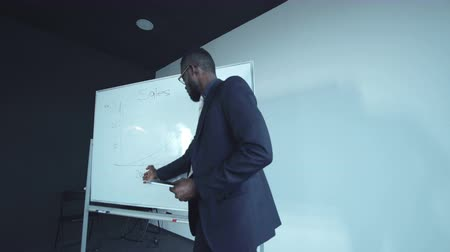 placa : African businessman holding a tablet and presenting the diagram drawn on the board.
