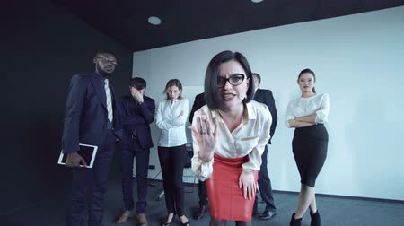 нет людей : A woman walking out of people circle and gesturing no payment during the work meeting.