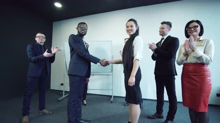 Поздравляю : The black businessman shakes hands with the colleague the Asian business woman, against the background of the applauding colleagues. They reached the agreement and signed the contract