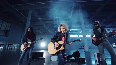 playing band : Low angle camera quickly zooming in shooting rock band playing guitars with curly woman in leather jacket singing and two men standing on sids. Indoors empty dark hall