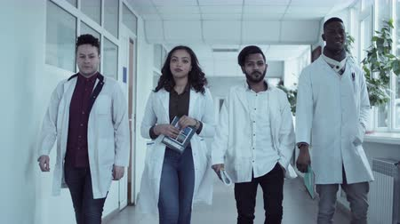 белый : Four multiethnic medical university students in white coats walking in corridor, holding copybooks and smiling. Front view