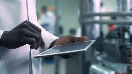 érintés : Close-up video of incognito Afro-American scientist hands in white lab coat holding a tablet and clicking on it while standing in laboratory Stock mozgókép