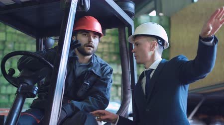 yükleyici : A businessman explaining to the driver the work in the warehouse. Horizontal indoors shot.