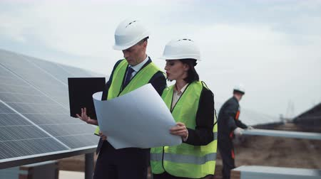 yönetici : The engineer supervisors standing with blueprint between row of solar panels and discussing construction plan using notebook laptop. They checking setup quality during workers mount on construction on background