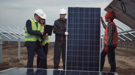 munkahelyek : The group of people standing and holding a solar energy panel while looking at camera between row of panels on solar farm. Main engineer explain how to setup panels using laptop