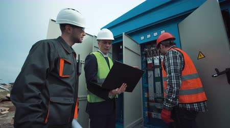 felügyelő : The group of electricians and engineers stand near the transformer of the electric power and discuss blueptints using the computer