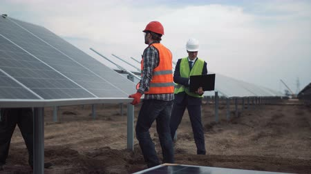 устанавливать : The engineer controls installation process of solar batteries, two employees in a uniform and in hardhat.