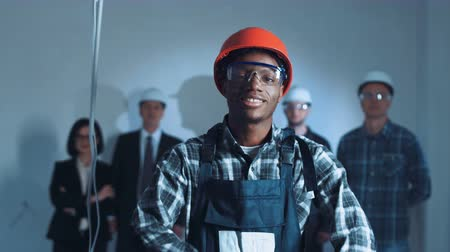 karbantartás : An African builder putting on the protective glasses and headphones and red hard hat. On background builders and manager team