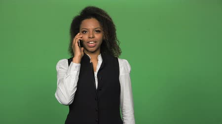 формальный : Young african business woman in formal suit answering and talking phone isolated on green background.