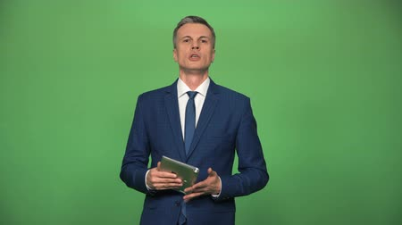 описание : Visagiste powdering male in suit before he performing with tablet in hands on green background.