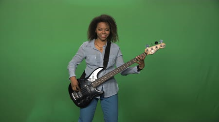 electric : Young black female in shirt playing electric guitar standing on green background.