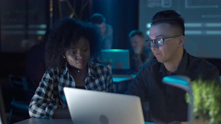 programmers : Young multiracial team sitting and working at the laptop and desktop computer together in a modern office. Stock Footage