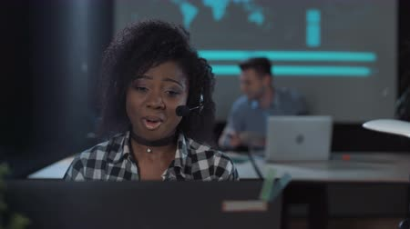консультант : Cheerful African woman with headset in call center talking and looking at screen of desktop computer
