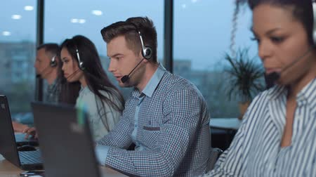 Men with headset working in call center in modern worldwide office he talking and looking on screen of desktop computer solving the clients problem