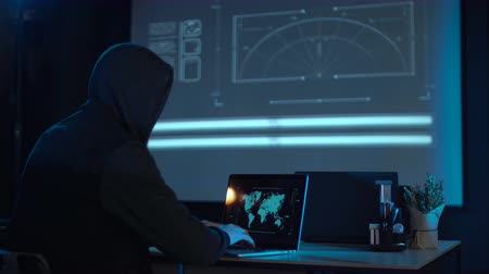 süzülme : Man in the hood from his back sitting and working at laptop as hacker, with world map on wall in background. Then he take off usb flash disk and run away. Perhaps he has stolen information or has cracked system and has loaded a virus.