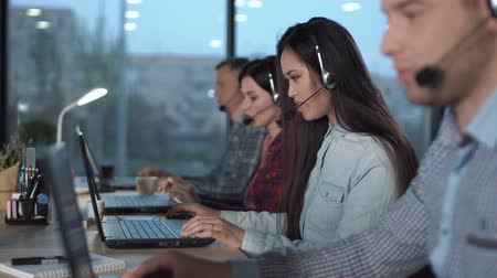 clientes : Young Aasian woman with headset working in call center in modern worldwide office talking solving customers problems