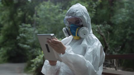 környezeti : Anonymous biologist in environmental suit browsing tablet in woods.