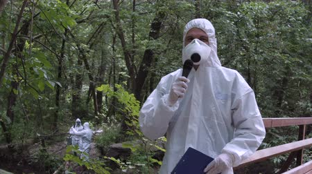 környezeti : Man wearing protective suit holding file in hands and speaking microphone while looking at camera on nature. Stock mozgókép