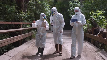 környezeti : Three scientists wearing white protective suits standing on road in countryside discussing. Stock mozgókép