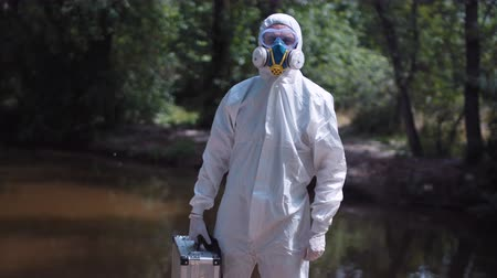 vizsgálat : Anonymous male biologist in white protective suit posing with silver toolbox in hands on background of nature, red dirty river. Stock mozgókép