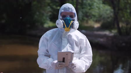 környezeti : Anonymous female biologist in white protective suit posing with tablet in hands on background of nature. Stock mozgókép