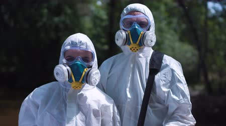 környezeti : Group of two biochemists in protective suits posing and looking at camera on background of nature.