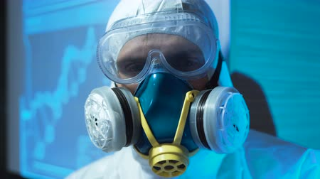 bio hazardous : Person in a laboratory wearing a biohazard suit and mask with breathing apparatus while working with hazardous toxic material