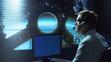 security agencies : Side view of supervisor man in headset sitting and working in space mission control center. Stock Footage