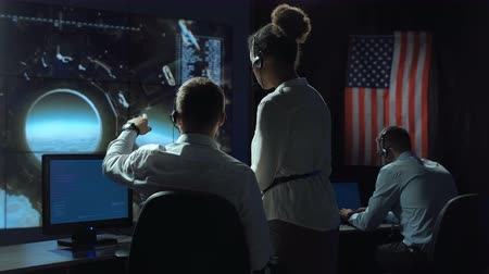 security agencies : Back view of man pointing and showing to woman in space flight control center. Moon landing of spaceship module.