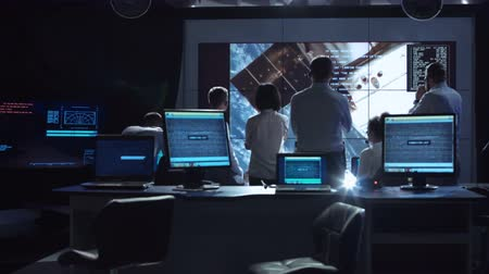 управление : Back view of people working and managing flight in mission control center. Elements of this image furnished by NASA.