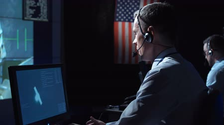 security agencies : Side view of supervisor man in headset sitting and working in space mission control center. Watching flight of satellite. Elements of this image furnished by NASA.