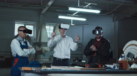 fejhallgató : Workers and foreman using virtual reality headsets in carpentry workshop.