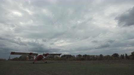 ZAPOROZHYE, UKRAINE - October 10, 2017: Small aircraft landing in field on cloudy day. Stock mozgókép