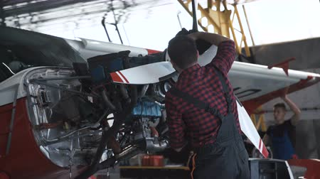 rotational : Bearded man cleaning airplane propeller in hangar