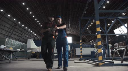 szerelő : Two flight engineers walking through a large aircraft hangar talking and gesturing together