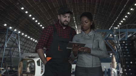 piloto : Man standing and discussing over digital tablet in aircraft hangar with woman Stock Footage