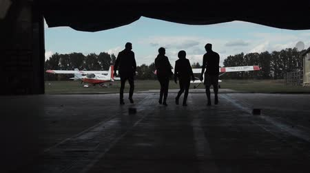 навес : Slow motion of group of people walking through hangar and then leaving it.