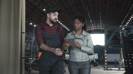 piloto : Man go and discussing over digital tablet in aircraft hangar with black woman Stock Footage