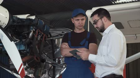 навес : Mechanic standing near plane, looking at engine and talking to draftsman.