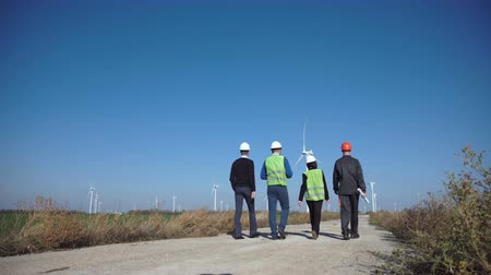 rotational : Side view of four engineers wearing hardhat walking against turbines at wind farm on sunny day Stock Footage