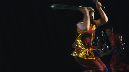 quimono : Slow motion of group of confident warriors presenting art of wushu fighting techniques on black background with swords and spears. Shot on RED cinema camera.